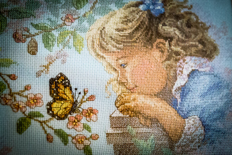 little girl with blonde curls inspecting a butterfly, cross-stitch embroidery art