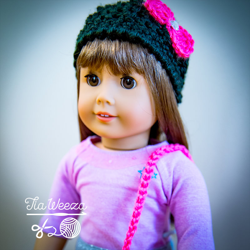 square aspect american girl doll wearing black and hot pink crochet beanie with coordinating booties purse.