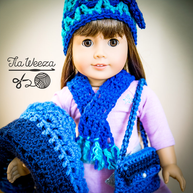 square aspect american girl doll wearing deep blue and turqouise beanie, scarf and booties with coordidnating afghan and purse.