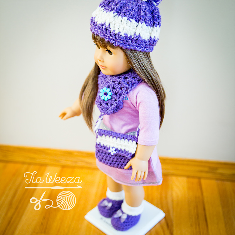 square aspect american girl doll wearing cozy purple crochet beanie and scarf, with coordinating booties purse and blanket.
