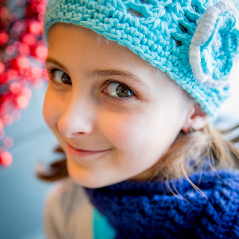 happy little girl wearing a robin egg light blue crocheted hat with a flower and dark blue scarf