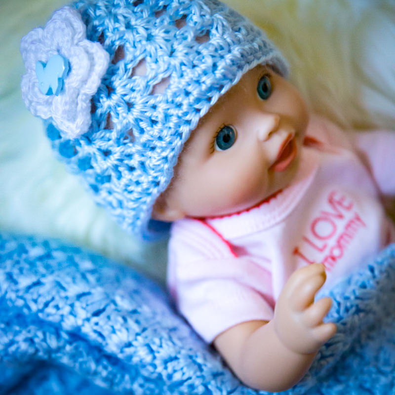 baby doll wearing handmade crocheted hat and blanket in light blue