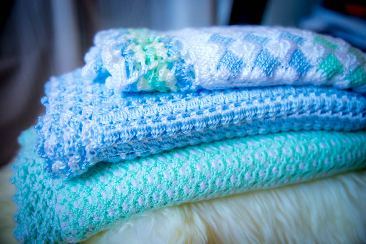 stack of crochet newborn blankets side view