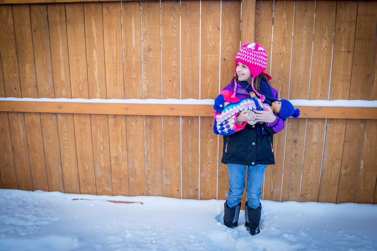 little girl wearing a knit hat and scarf with american girl doll wearing handmade matching accessories