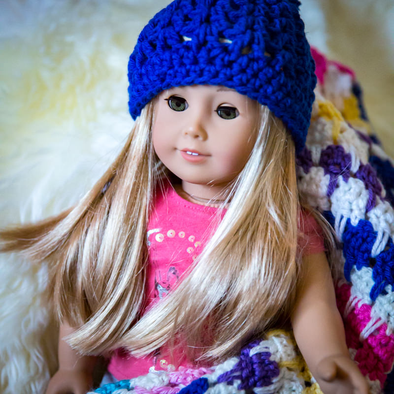 american girl doll wearing handmade crocheted hat with blanket